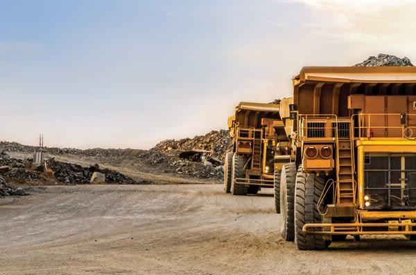 dump-trucks-carrying-ore-sunset